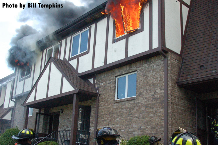 Fire vents through the roof of a town house