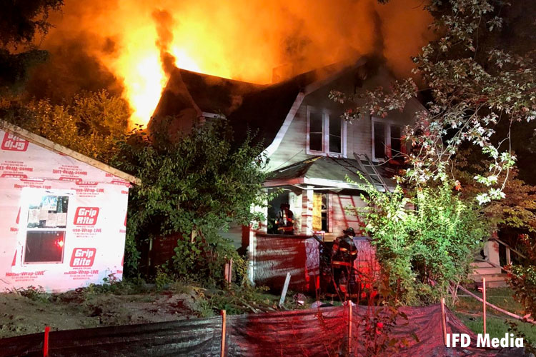 Firefighters confront a fire in an abandoned home