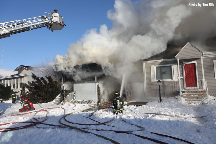 Firefighter with hoseline and firefighter in tower ladder at house fire in snow