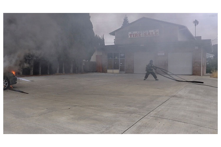Firefighter pulls a line at a vehicle fire