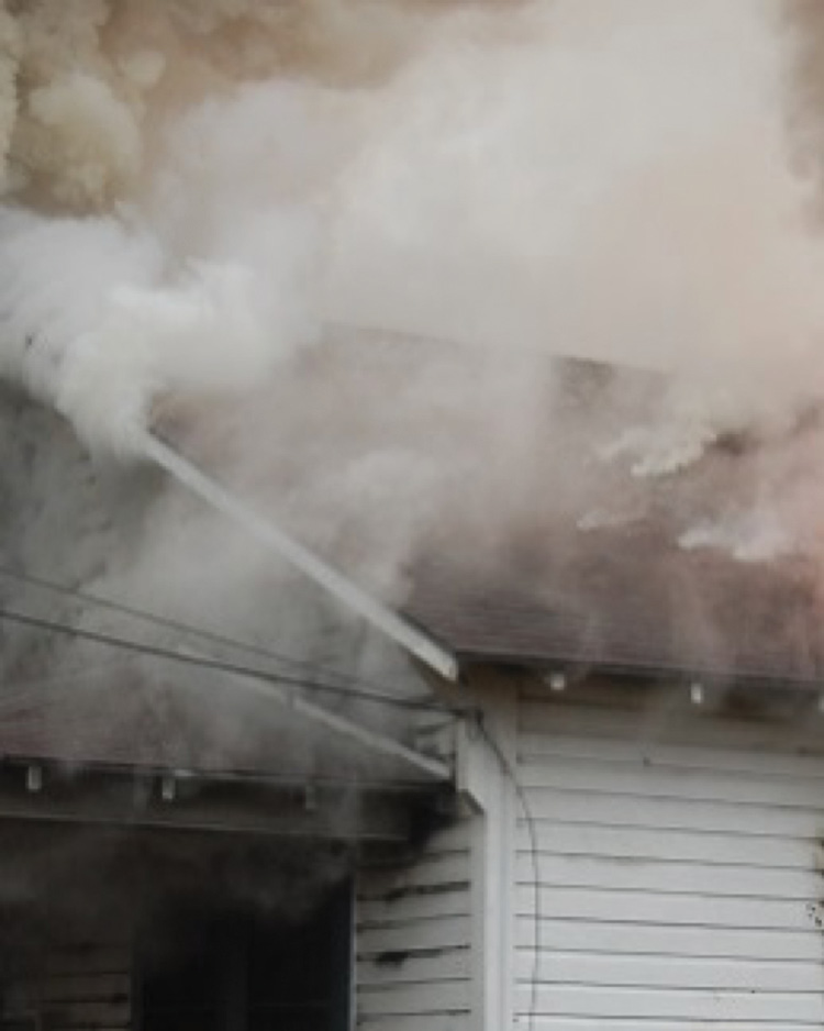 The clean white smoke coming from roofing materials is conductive heating steam, resulting from the fire in the attic space below. (Photo by Dave Dodson.)