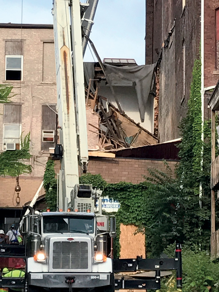 The abutting B side exposure and the collapsed roof of the two-story C side addition, the scene during the rescue after the secondary collapse. (Photo by John Soderberg.)