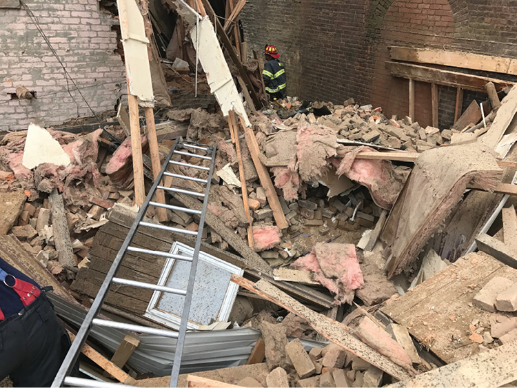 This ladder was used as a bridge across the collapsed roof rubble between the back of the C side (at left) and exposure B side (at right). This was the initial access path to the victim.(Photo by Christopher Chiprich.)
