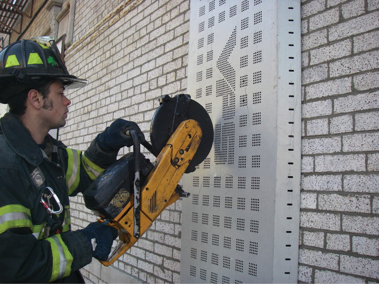 (12) This firefighter is cutting the VPS bars inside the window guard.