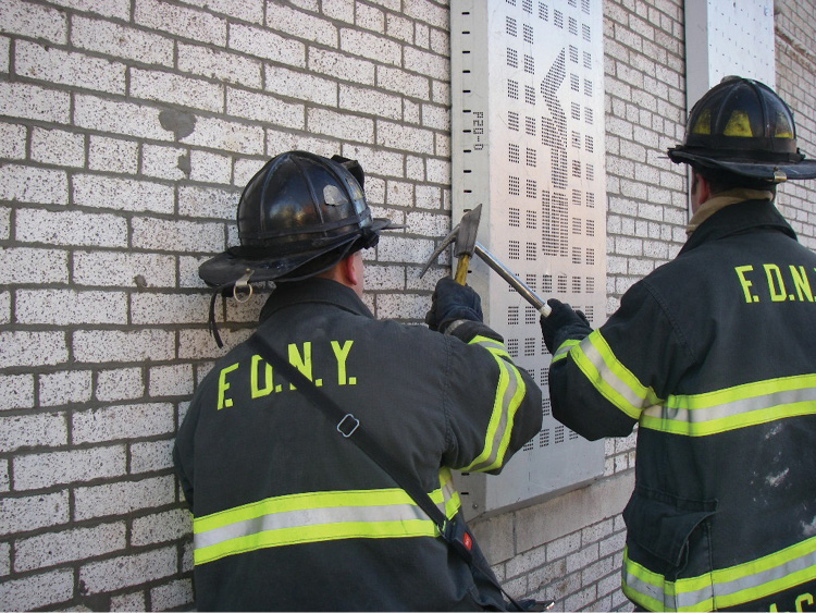 (13) Firefighters are using forcible entry tools to pry the window covering off.