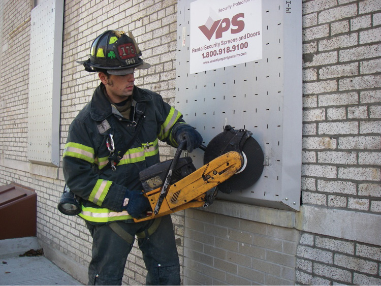 (16) A firefighter uses a saw to cut the bolt head on a cable-type VPS window guard.