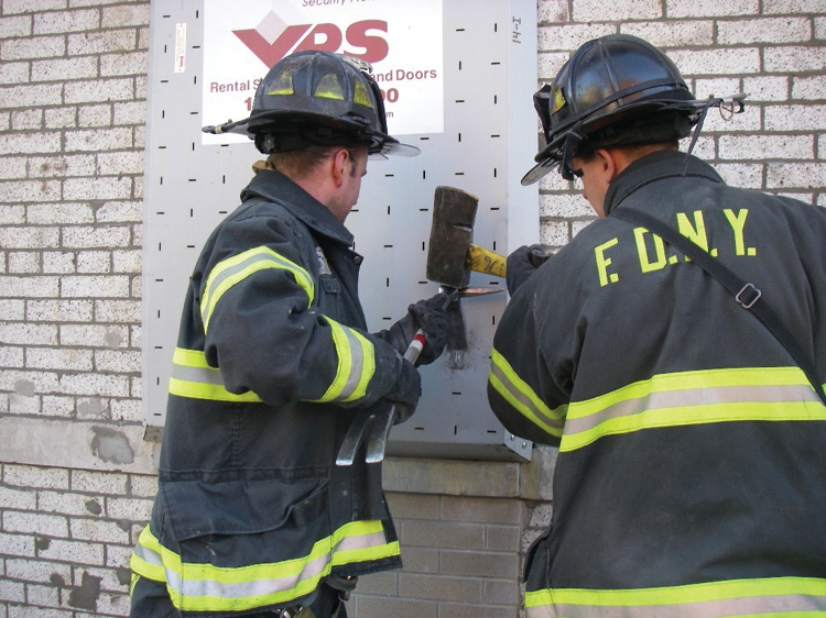 (17) Firefighters use forcible entry tools to shear the bolt head on a VPS window guard.