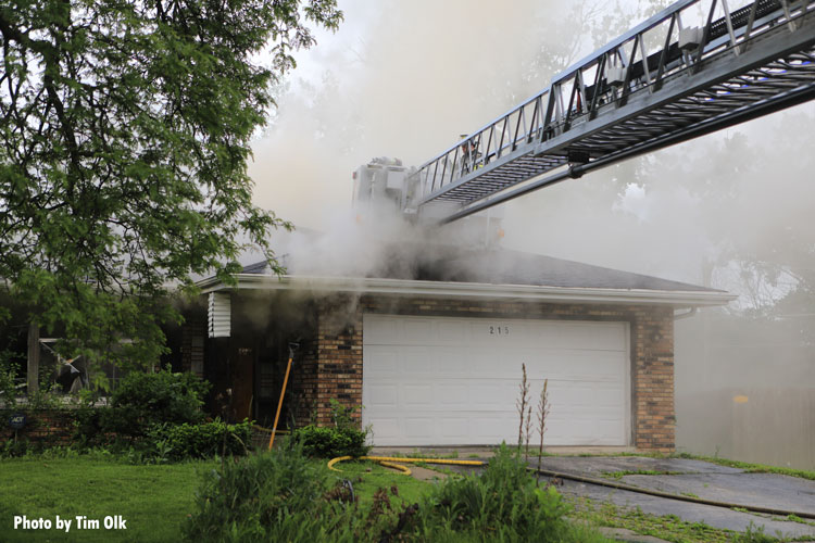 Tower ladder bucket over house fire