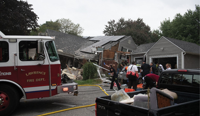 The fire and explosion on Chickering Street caused one death and three injuries. Rescue workers assess and attempt to extricate the victim in the auto. (Photos by Kevin D. White unless otherwise noted.)
