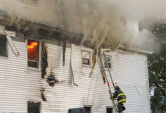 Brookfield Street: A firefighter climbs a ladder to attempt to ventilate the fire building. (Photo by SmokeShowingPhotography.com.)
