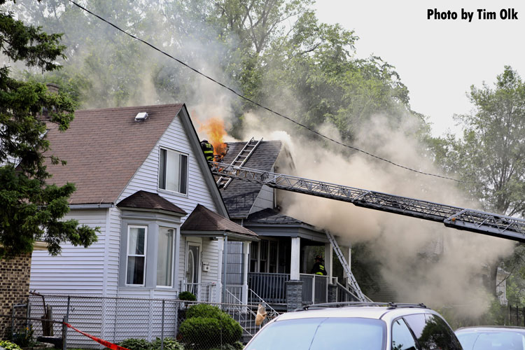 Chicago firefighter on a ladder with fire venting through the roof