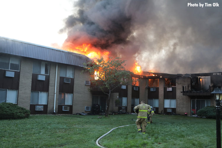 Firefighters approach a burning apartment building
