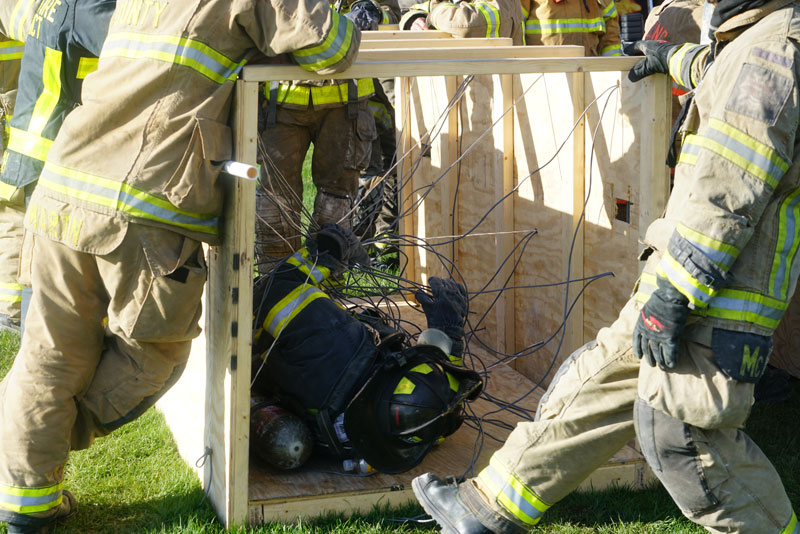 A firefighter trains on self-extrication after being entangled in wires