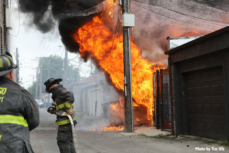 Chicago firefighter with a hoseline as fire rages in the background
