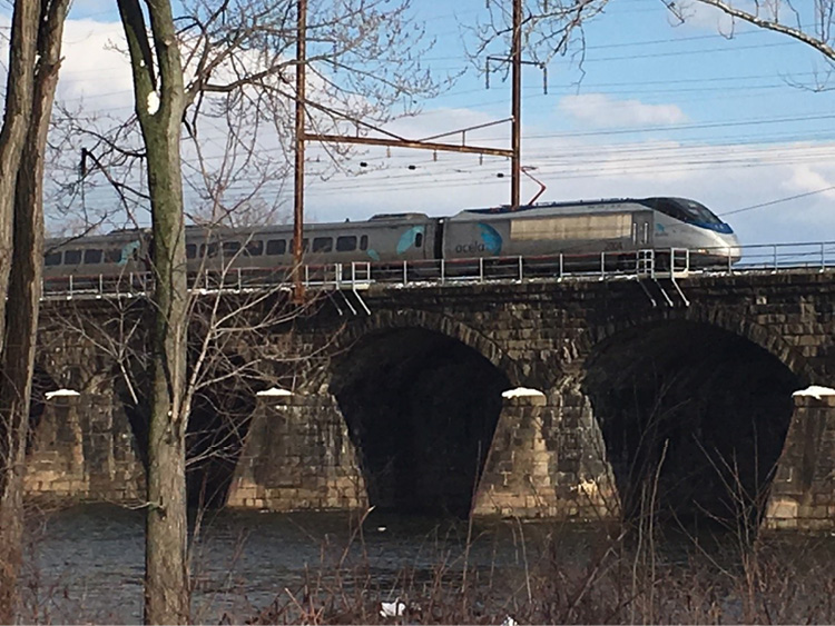 """An Amtrak Acela train crossing the Delaware River from Trenton, New Jersey, to Pennsylvania. The size-up for this train should include that it is an """"Amtrak high-speed passenger train with an electric locomotive in electrified territory on a bridge over water"""" followed by the type of emergency (e.g., fire, derailment). This will help determine the type of additional resources needed, the proper command center, and the emergency management contact for removing power and stopping the train."""