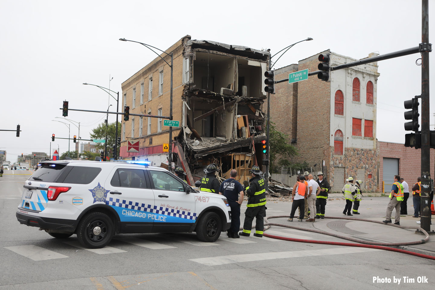 A Chicago police car and Chicago firefighters on scene.