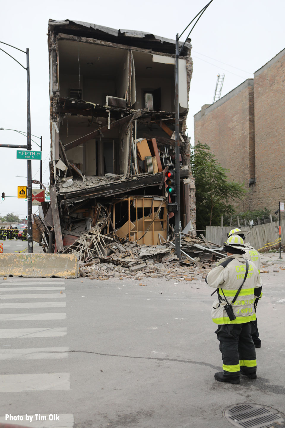 A Chicago fire official with the damaged building in the background.