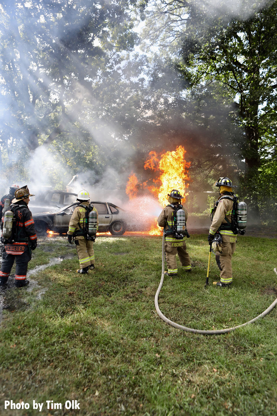 Firefighters operate a hoseline at a garage fire with extension.