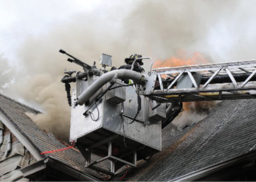 The tower ladder sticks the valley, granting access to multiple sections of the roof, allowing the firefighters to cut both sides from the bucket. (Photo by Patrick Dooley.)