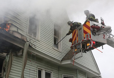 The outside vent firefighter takes an upper-floor window from the bucket of the tower ladder. (Photo by Patrick Dooley.)
