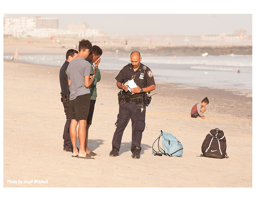 NYPD officers speak with teens on the beach.