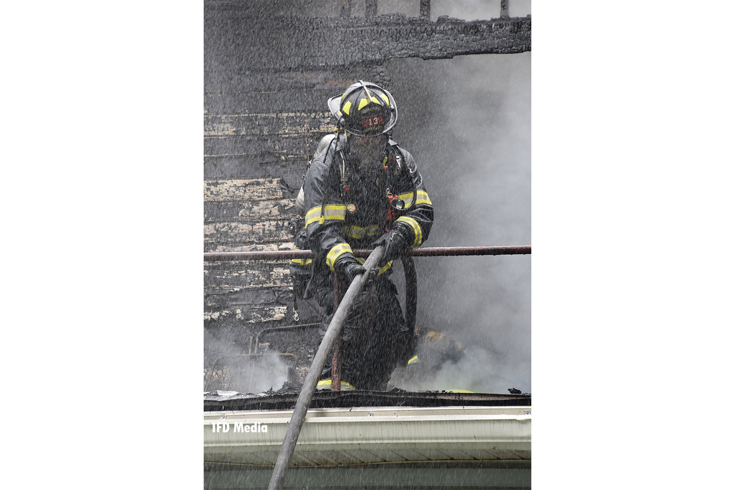 A firefighter hauls a hoseline up onto a roof.