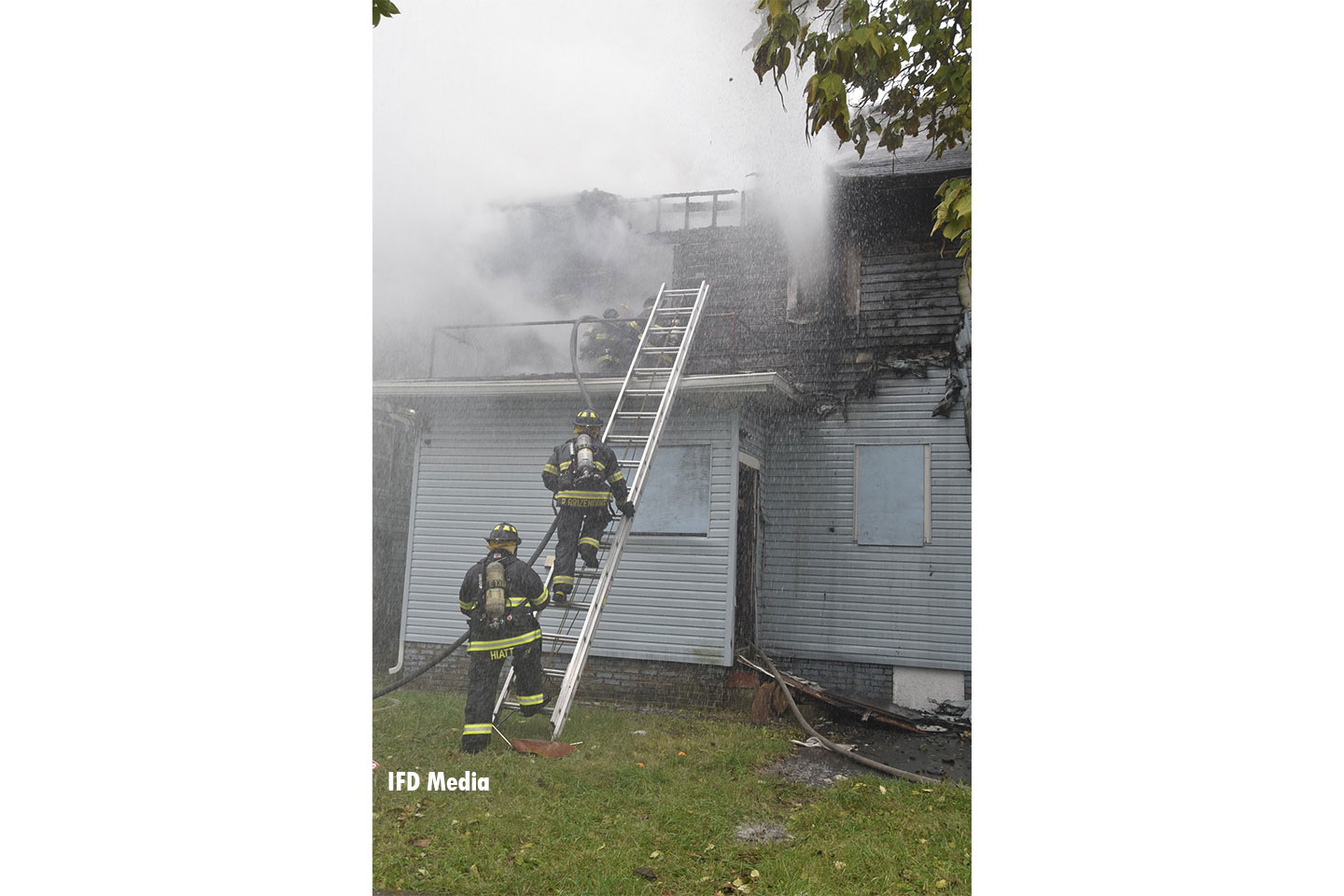 Firefighters advance a line up a ladder at the fire.