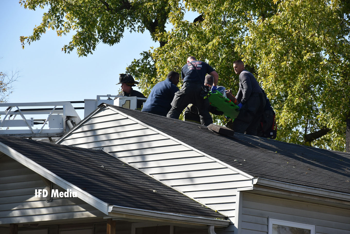 Firefighters rescue the injured patient from the home's roof