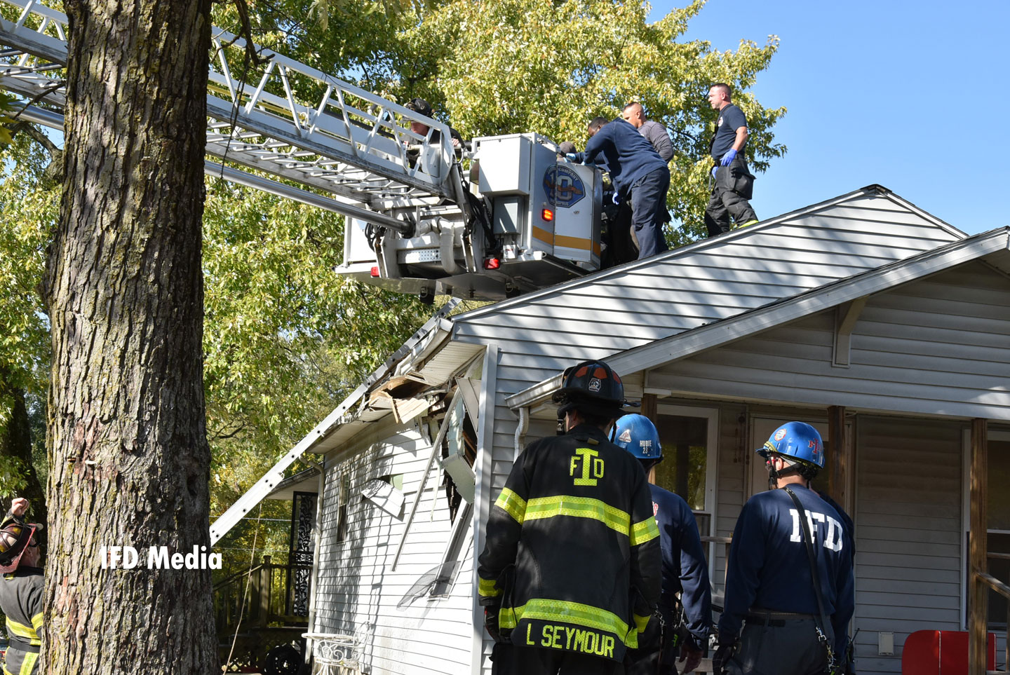 Firefighters operate out of a tower ladder bucket
