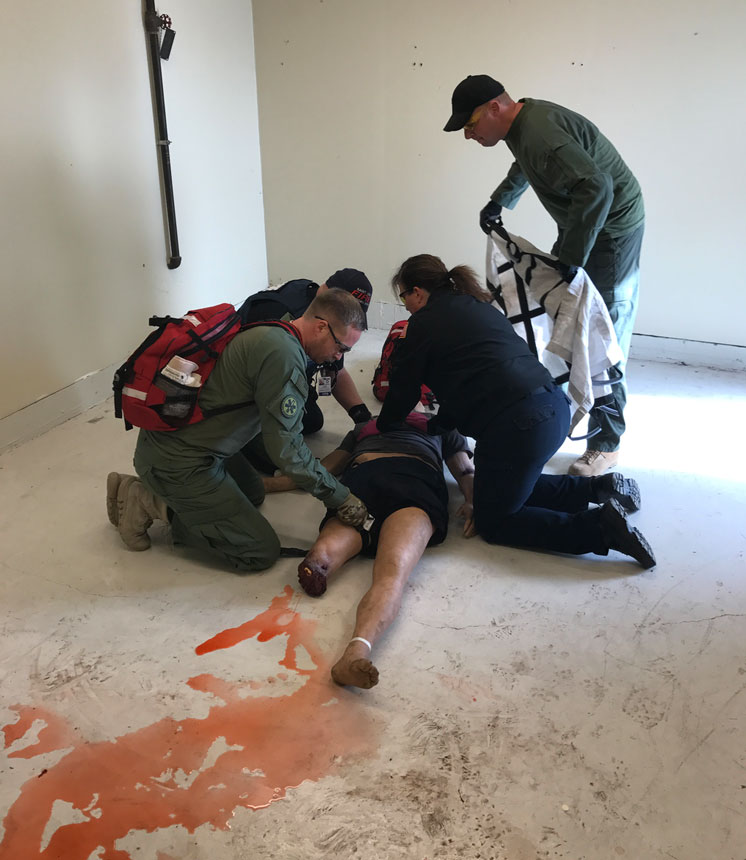 Responders attend to a victim during training.