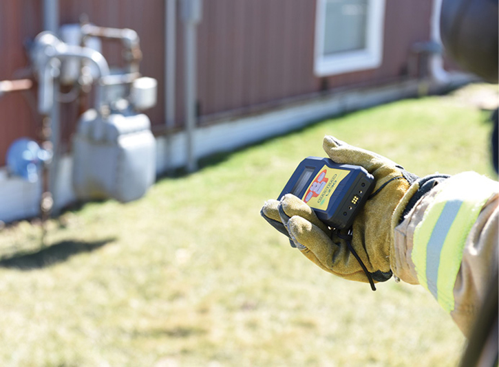 A firefighter points the handheld laser gas detector at a commercial meter to determine if gas is leaking.
