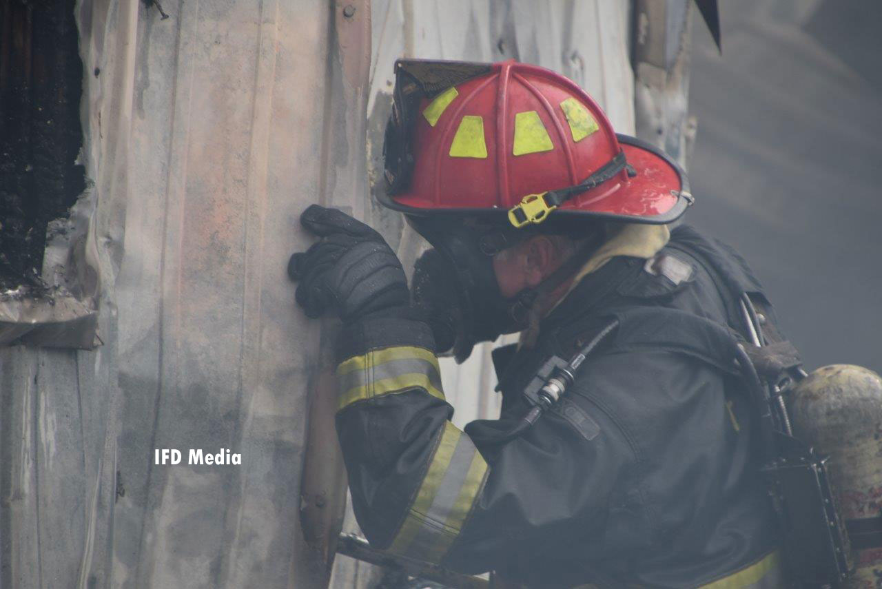 A firefighter peers into the structure