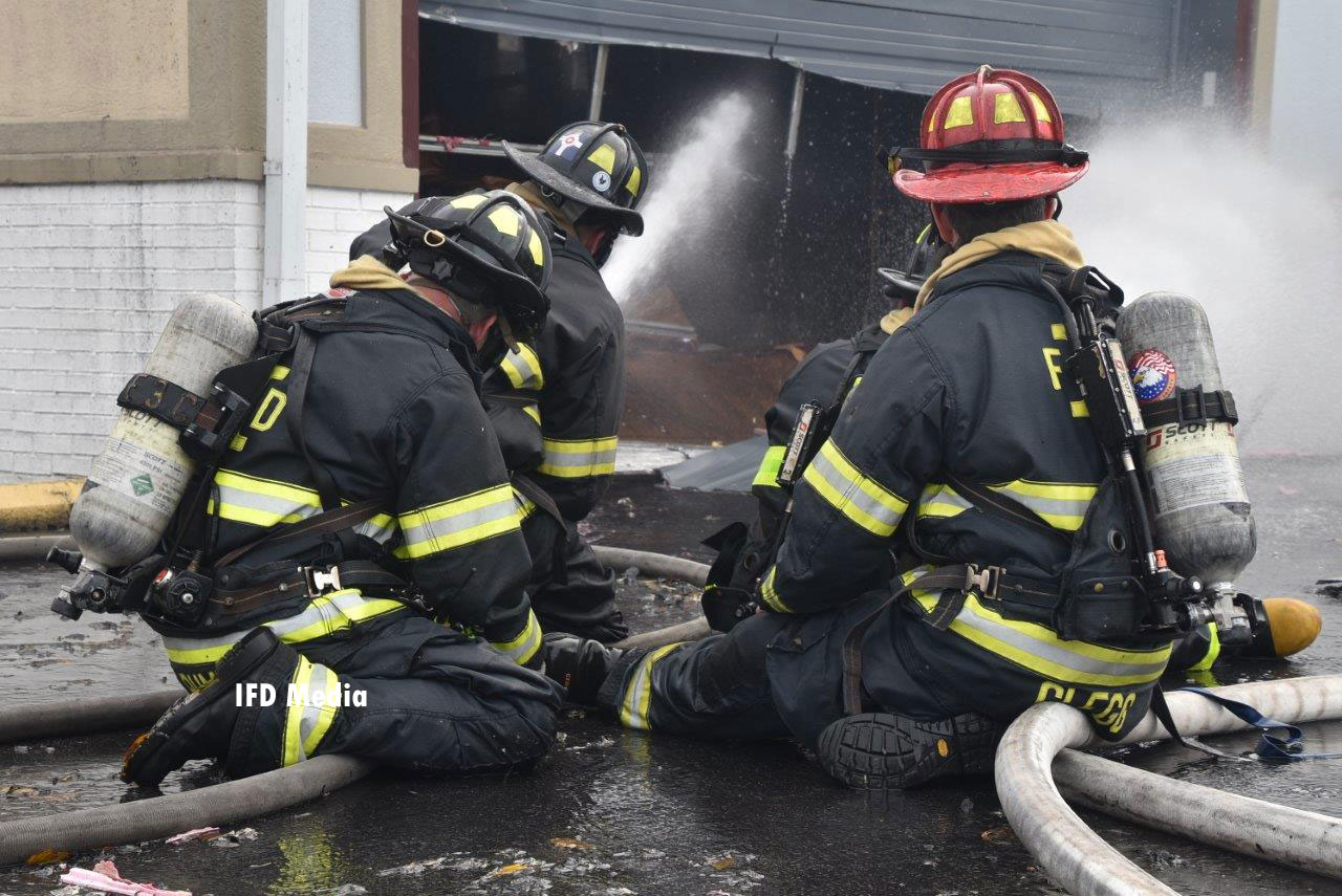 Two firefighters operating lines at the scene of the warehouse fire