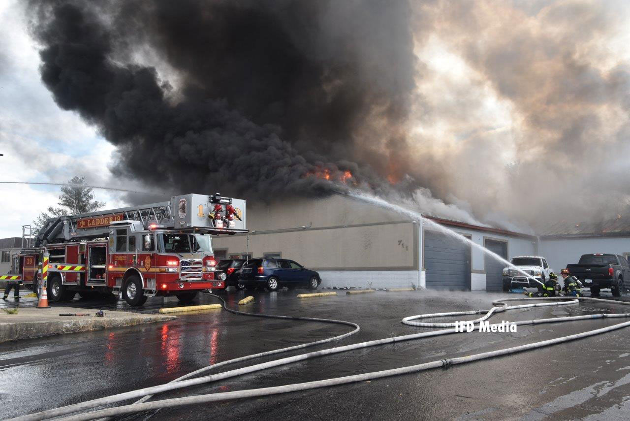 A tower ladder and firefighters operating a handline on the exterior of the building as flames and smoke vent from the roof