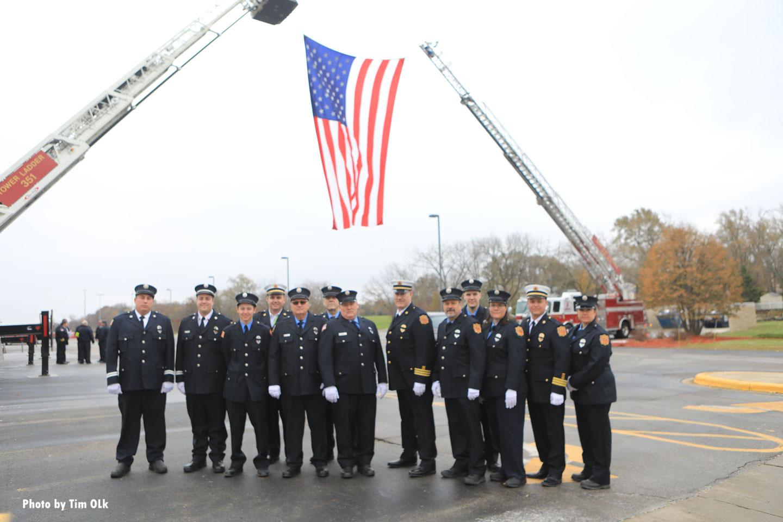 Firefighters beneath a huge U.S. Flag held by aerial ladders