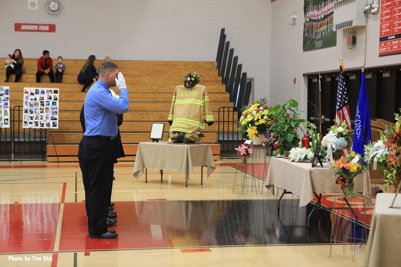 A firefighter salutes his fallen colleague