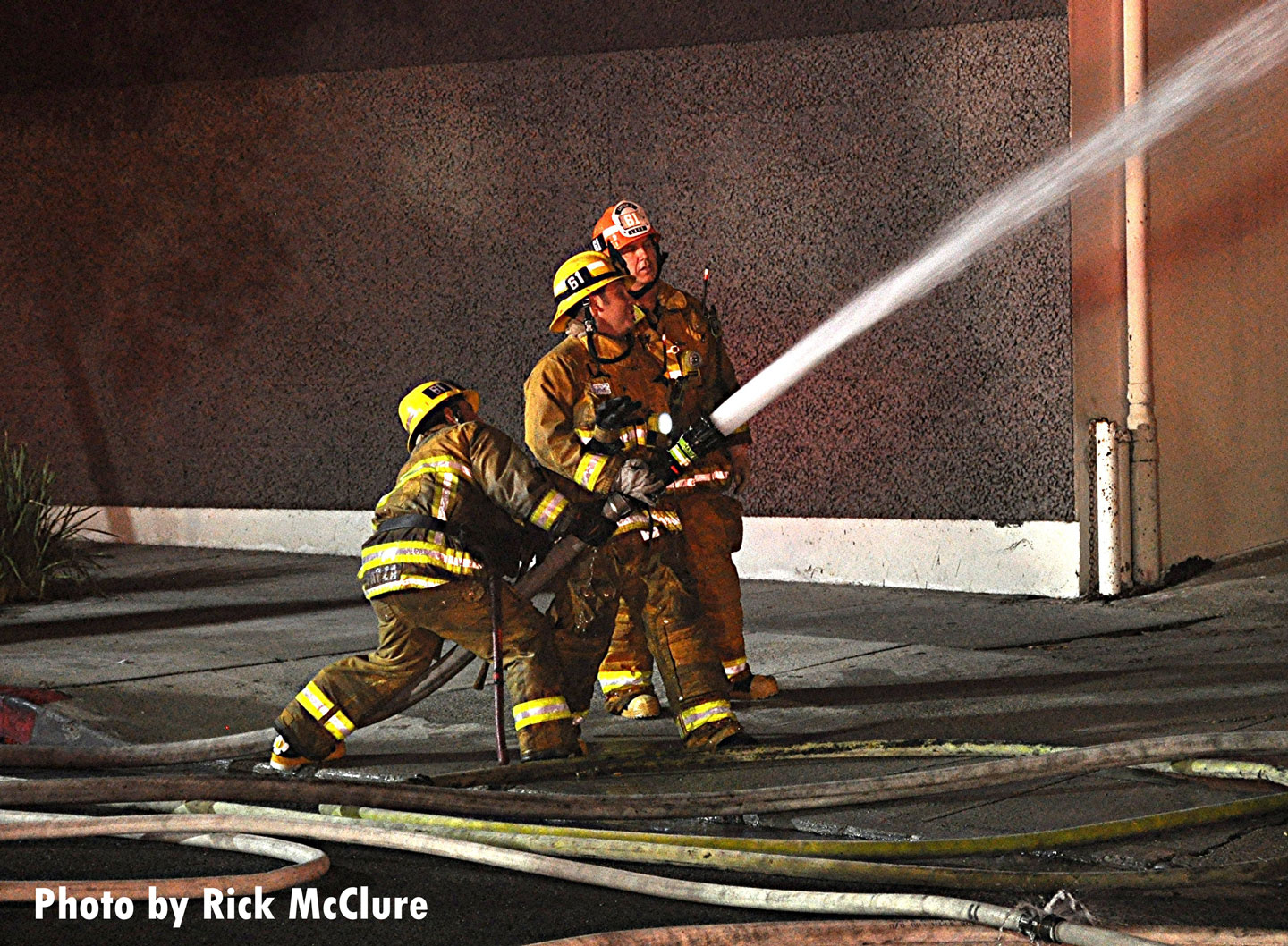 Firefighters control a stream on the exterior of the building.