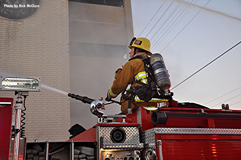 A firefighter aims a deck gun at the building.