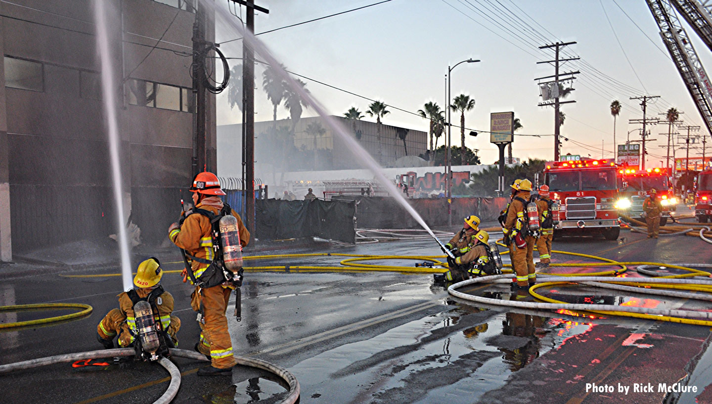 Firefighters control streams from the ground.