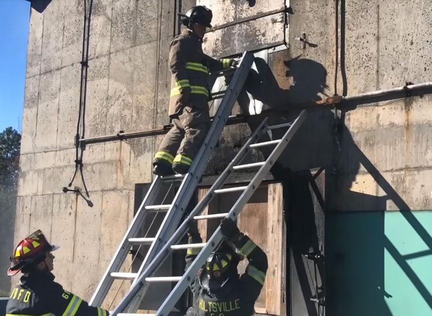 Firefighters raising ladders