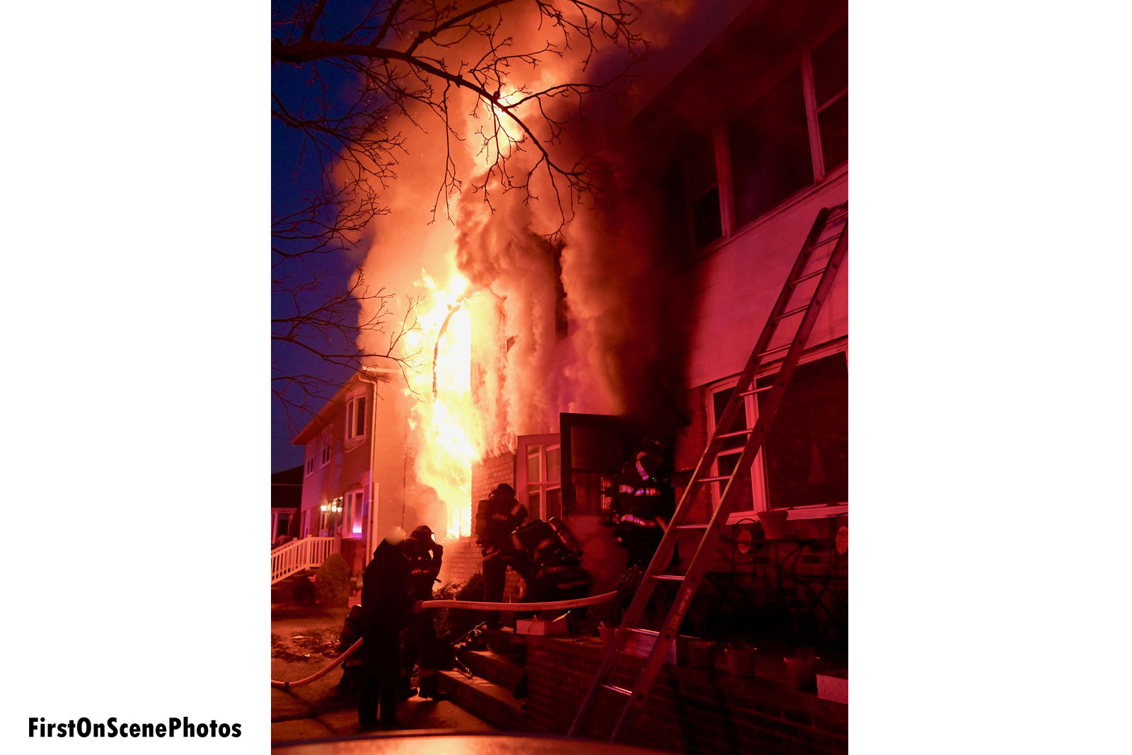 Firefighters put a line through the front door as flames vent from the side of the home