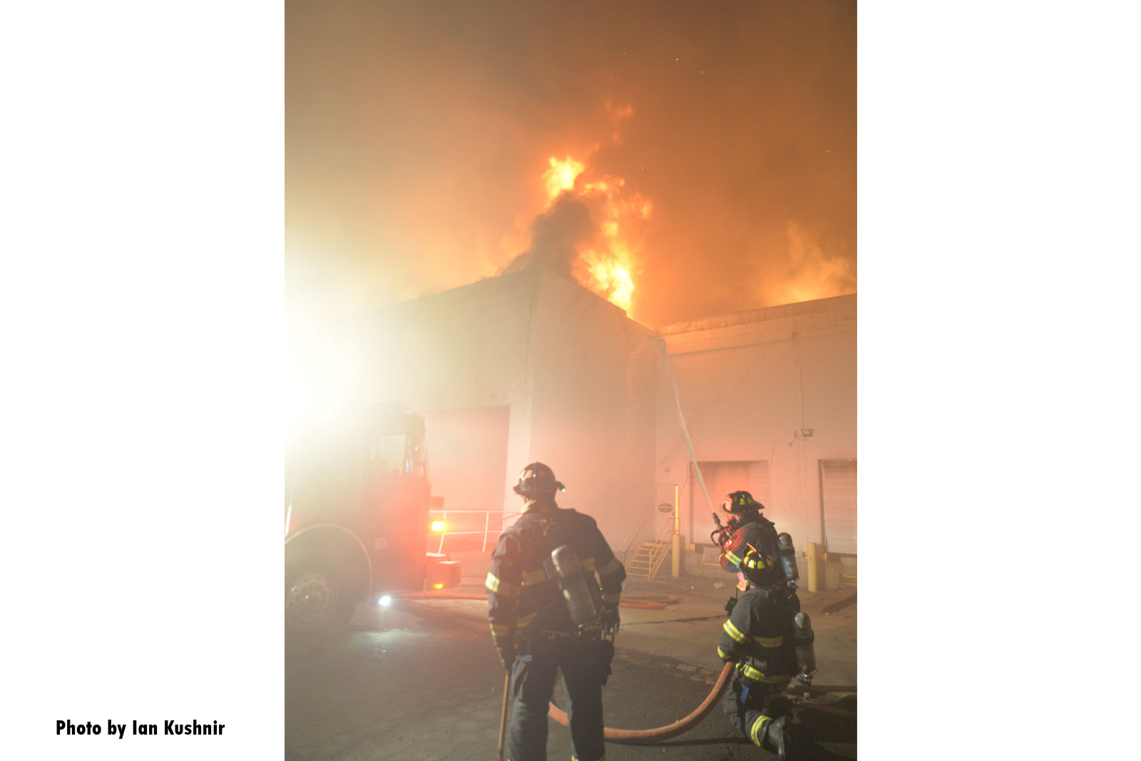 Firefighters working as flames erupt from the building