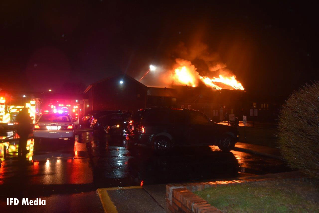 Firefighters responding to a fire in an apartment complex with reported entrapment.