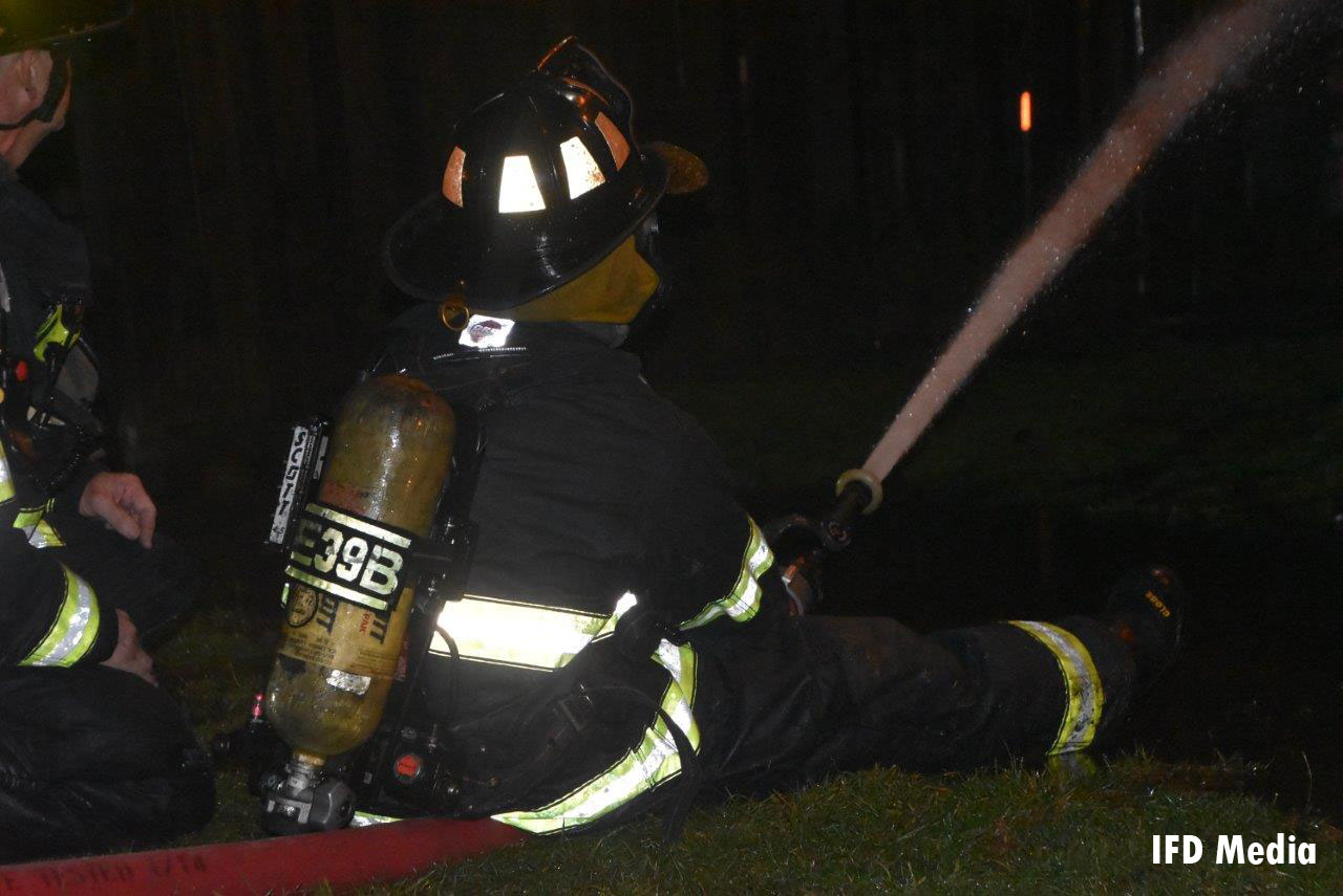 A firefighter controlling a line at the scene