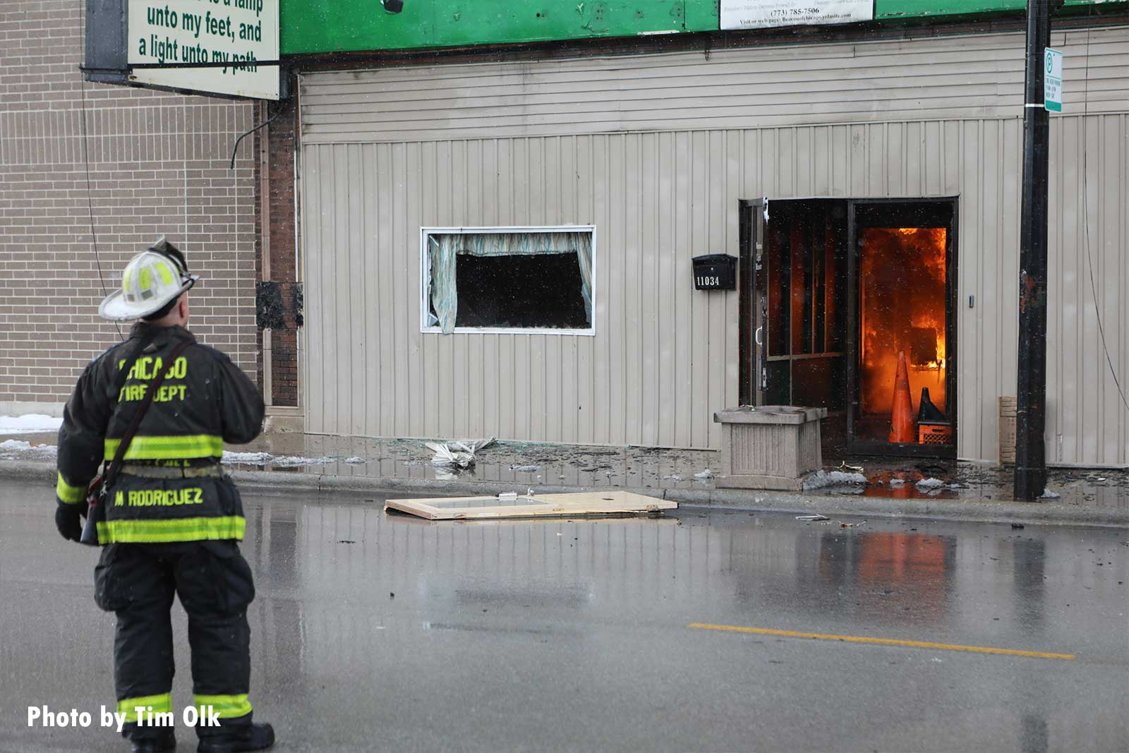 A firefighter with flames burning inside the building