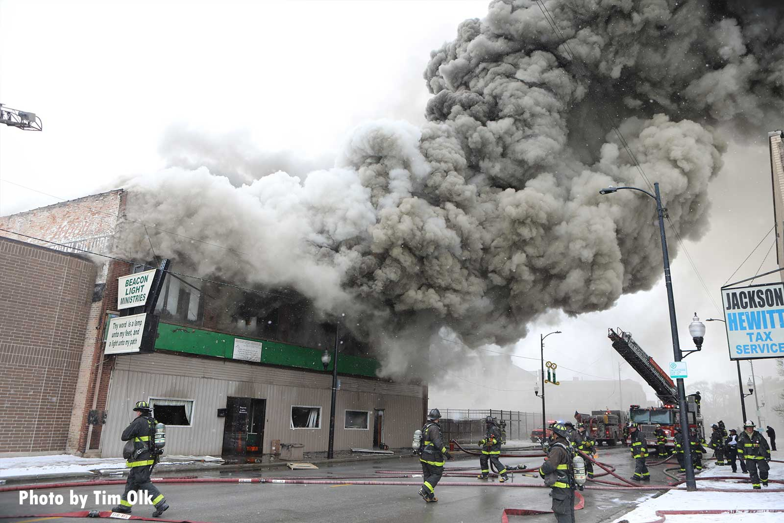 Chicago firefighters and hoselines at scene, with smoke billowing from the fire building
