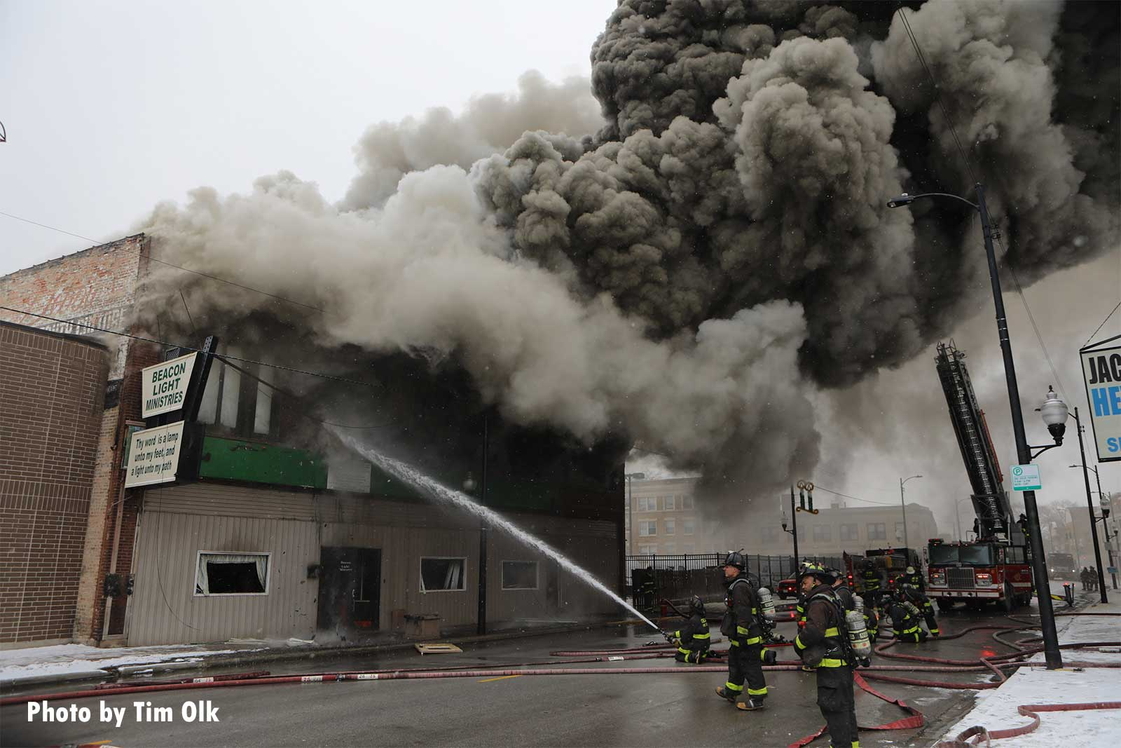 A firefighter directs a stream into the burning building