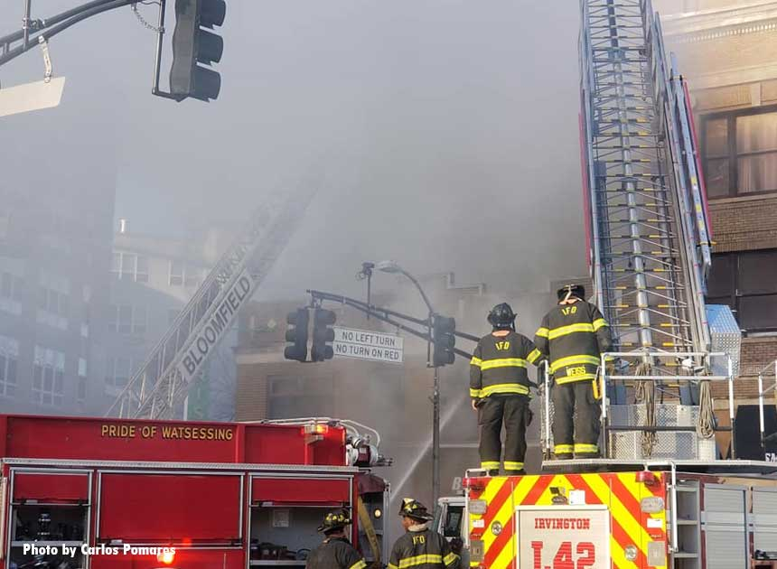 Firefighters on fire trucks with smoke hanging low overhead