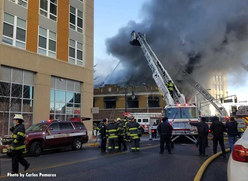 A view of aerial devices and smoke venting from the building