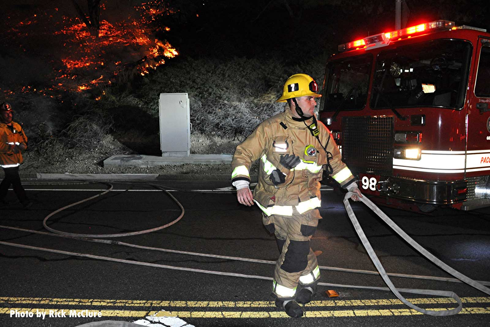 A Los Angeles firefighter flakes out a hoseline at the fire